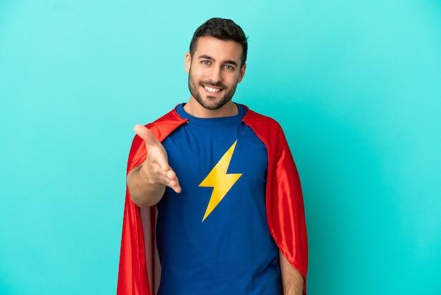 Homem super-herói, caucasiano, isolado em fundo azul, apertando as mãos para fechar um bom negócio