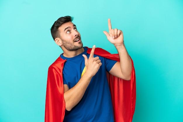 Homem super-herói caucasiano isolado em fundo azul apontando com o dedo indicador uma ótima ideia