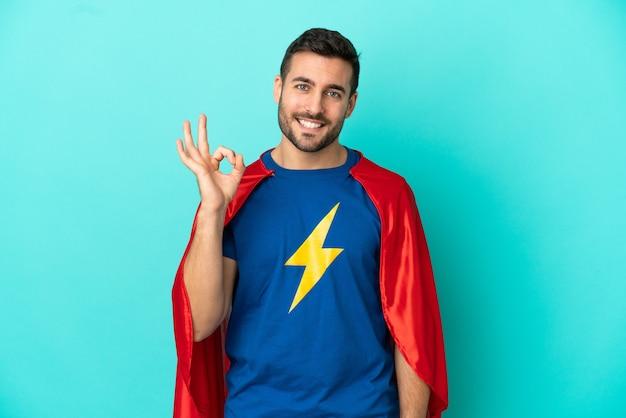 Homem super-herói caucasiano isolado em fundo azul, mostrando sinal de ok com os dedos