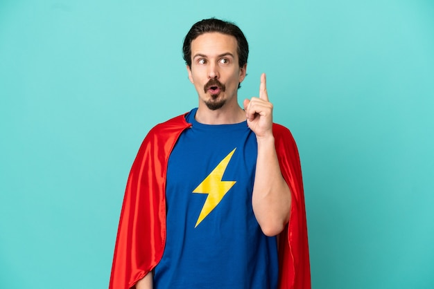 Homem super-herói, caucasiano, isolado em um fundo azul, pensando em uma ideia apontando o dedo para cima