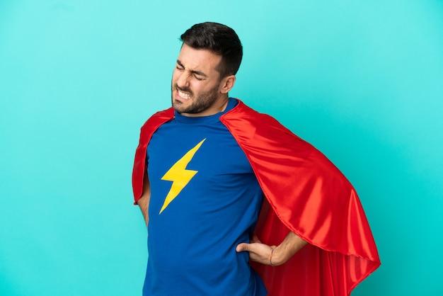Homem super-herói, caucasiano, isolado em um fundo azul, sofrendo de dor nas costas por ter feito um esforço