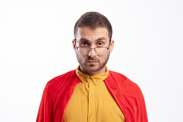 Homem super-herói confiante usando óculos óticos com capa vermelha olhando para a frente, isolado na parede branca