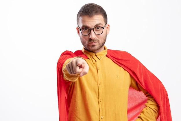 Homem super-herói confiante usando óculos óticos com pontas de capa vermelha na frente, isoladas na parede branca
