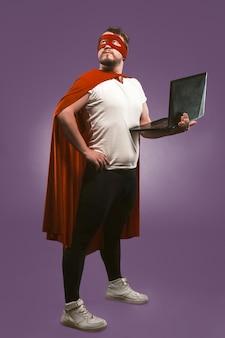Homem super herói detém um laptop olhando pensativamente. homem de negócios em traje de super-herói vermelho usando o computador posando em fundo roxo uva. conceito de internet rápida