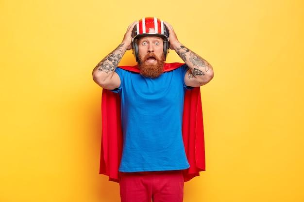 Homem super-herói emocional amedrontado olha maravilhado para a câmera, mantém as mãos no capacete