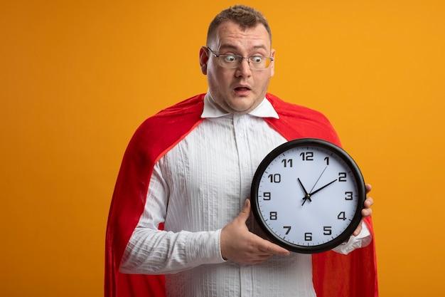 Homem super-herói eslavo adulto impressionado com capa vermelha usando óculos, segurando e apontando para o relógio isolado na parede laranja com espaço de cópia