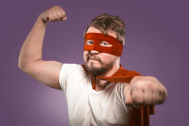 Homem super herói mostra os músculos com punho para a frente, olhando para a câmera. feche o retrato. foco seletivo no rosto masculino. homem forte em fundo roxo uva
