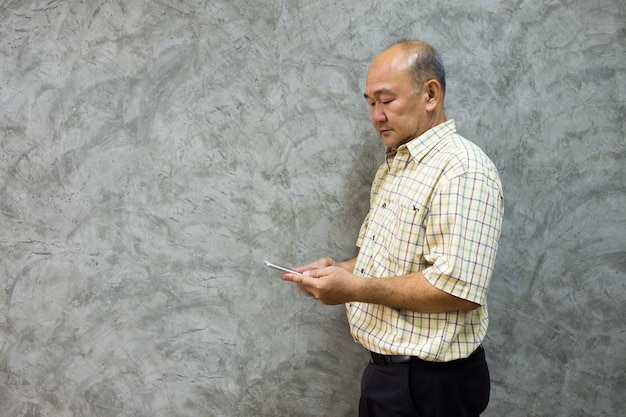 Homem superior asiático que usa o suporte do smartphone com fundo concreto cinzento.