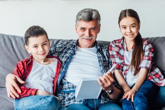 Homem superior com os dois netos bonitos que leem um livro ao situar no sofá.