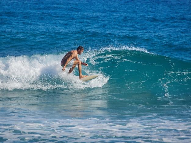 Homem surfando no oceano atlântico.