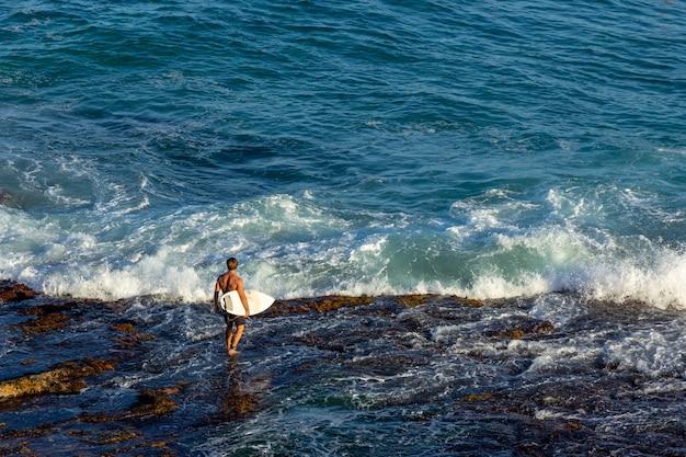 Homem, surfista, carregar, seu, surfboard, e, esperando, para, a, ondas, ligado, oceânicos