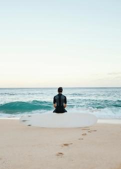 Homem surfista olhando para o mar em tiro plano vertical