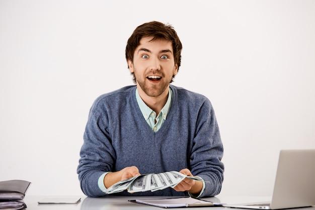 Homem surpreendido e animado expressa alegria como contar dinheiro, recebeu muito dinheiro, segurando dólares e olhando feliz