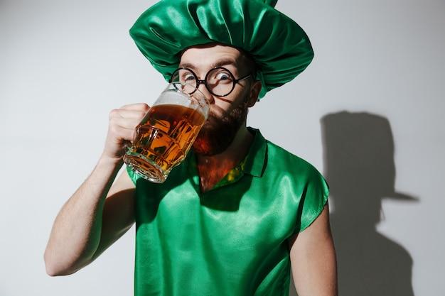 Homem surpreendido em traje de st.patriks, bebendo cerveja