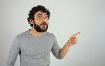 Homem surpreendido mostrando a direção e apontando com o dedo