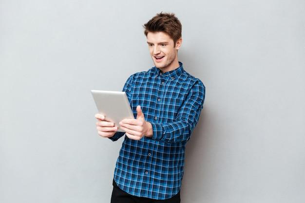 Homem surpreendido olhando para tablet computador isolado