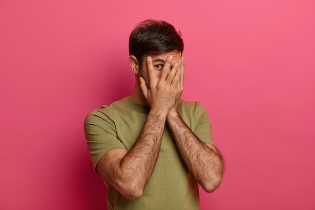 Homem surpreso cobrindo o rosto com as mãos, olhando por entre os dedos