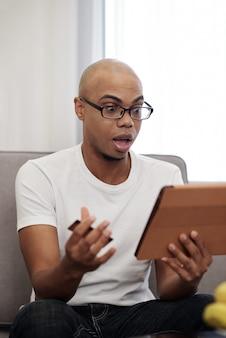 Homem surpreso com cartão de crédito olhando para tela de tablet de computador, pagando contas ou fazendo compras