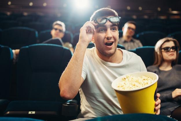 Homem surpreso com pipoca assistindo filme no cinema. entretenimento de cinema