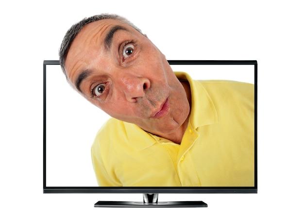 Homem surpreso com televisão e expressão wow na parede branca
