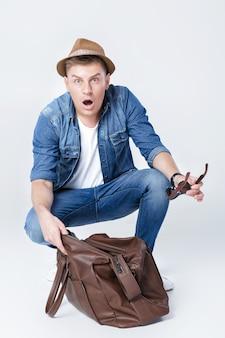 Homem surpreso de chapéu parece em uma bolsa de couro vazia o dinheiro tinha sumido