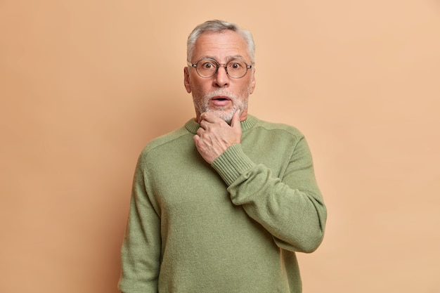 Homem surpreso e barbudo de cabelos grisalhos sem fala segura o queixo e encara os olhos esbugalhados ouve notícias secretas ou chocantes vestido com um macacão básico de mangas compridas isolado sobre a parede marrom prende a respiração de espanto