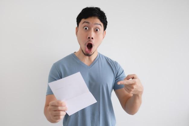 Homem surpreso e chocado com a carta em sua mão isolada.