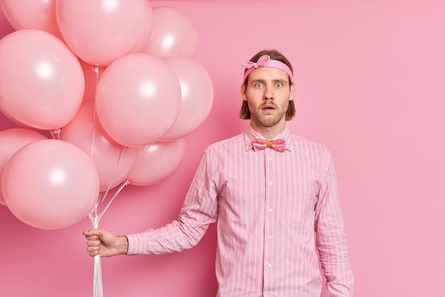 Homem surpreso e chocado segurando um monte de balões ouve notícias incríveis usa uma faixa na cabeça, uma camisa elegante com gravata borboleta comemora algo acontecendo na festa de aniversário isolada sobre a parede rosa