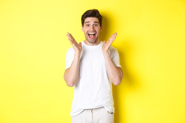 Homem surpreso e feliz reagindo ao anúncio, sorrindo e parecendo espantado, em pé contra um fundo amarelo.