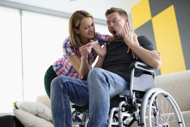 Homem surpreso em cadeira de rodas e mulher alegre olhando para teste de gravidez