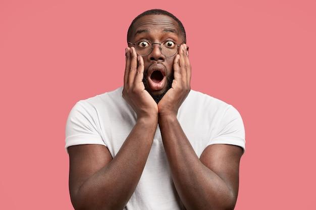 Homem surpreso mantém as mãos nas bochechas, abre a boca amplamente, reage a algo aterrorizado