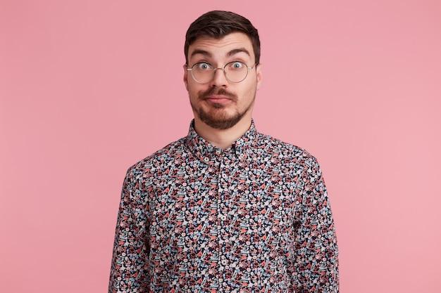 Homem surpreso que olha através dos óculos com mal-entendido, perplexidade, vestindo camisa colorida encolher os ombros na incerteza, sobre fundo rosa