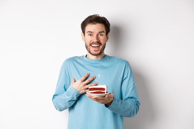 Homem surpreso recebendo bolo de aniversário com vela acesa, sendo parabenizado com b-day, arfando e espantado, em pé sobre um fundo branco.