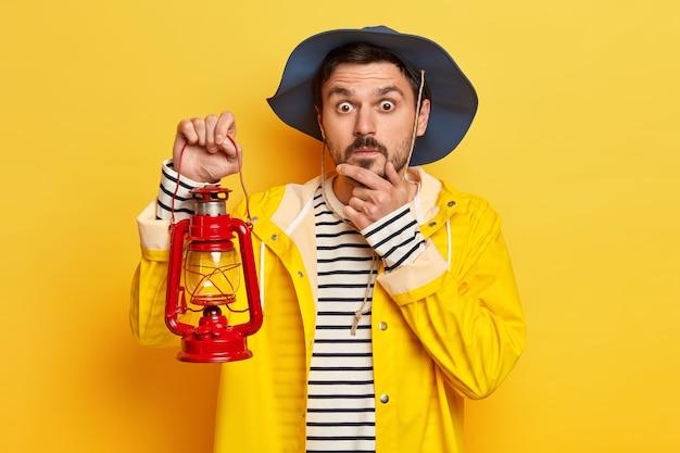 Homem surpreso, viajante mantém a mão no queixo, usa chapéu e capa de chuva, segura uma pequena lâmpada, explora poses de lugares interessantes contra a parede amarela