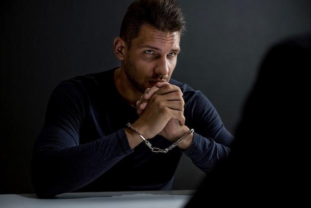 Homem suspeito ou criminoso com algemas na sala de interrogatório