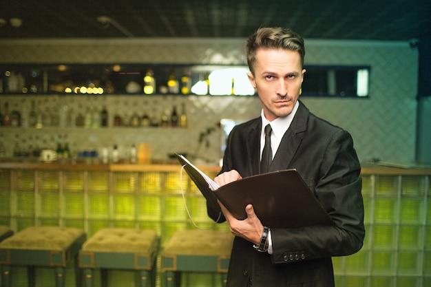 Homem suspeito verificando o menu dentro de casa no fundo do interior do bar do restaurante