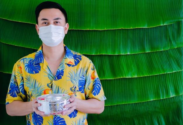 Homem tailandês com máscara facial, segurando a tigela de água com flores para abençoar o novo conceito normal do festival songkran.
