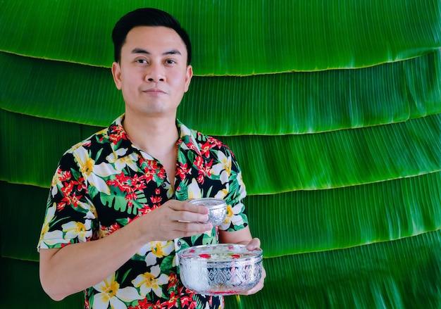 Homem tailandês segurando uma tigela de água com flores para abençoar o festival songkran com fundo de folha de bananeira.