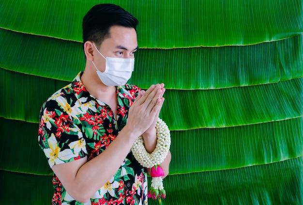Homem tailandês usando máscara facial fazendo postura de respeito com guirlanda de jasmim no braço para o novo conceito normal do festival songkran.