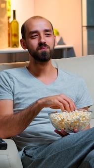 Homem tarde da noite em seu apartamento assistindo entretenimento na tv, rindo e se divertindo enquanto comia pipoca