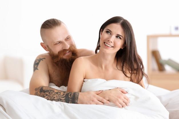 Homem tatuado com a namorada na cama em casa