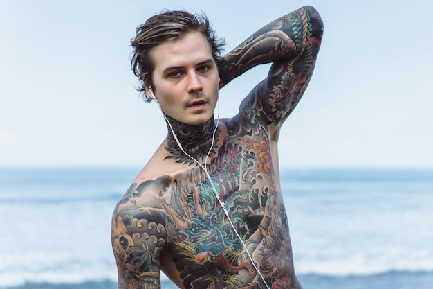 Homem tatuado com fones de ouvido contra o céu azul no oceano
