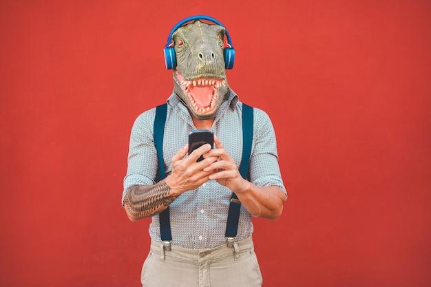 Homem tatuado com máscara t-rex usando smartphone enquanto escuta música - cara maluca sênior escolhendo lista de reprodução do aplicativo para celular - tendências tecnológicas e conceito de traje de loucura - foco no rosto