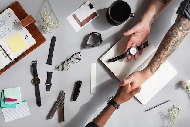 Homem tatuado e um homem negro de mãos dadas e um relógio