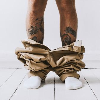 Homem tatuado pego com as calças abaixadas