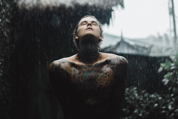 Homem tatuado posando na chuva
