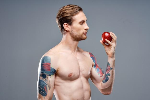 Homem tatuado, torso, músculos musculosos, esporte, fitness, maçã, saúde