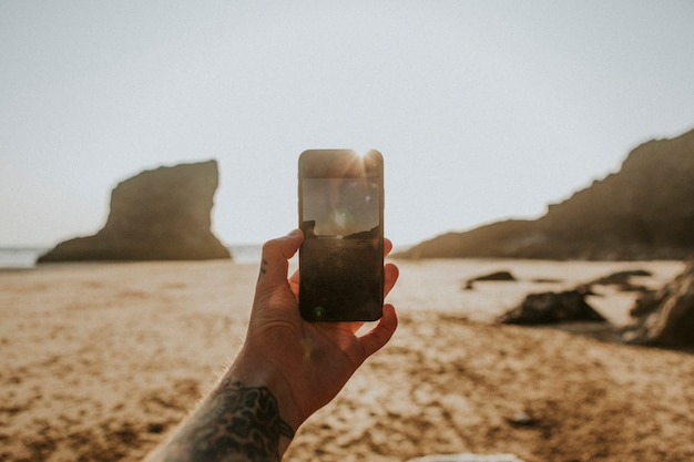 Homem tatuado usando uma câmera de celular na praia