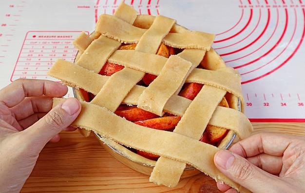 Homem tecendo à mão pedaços de massa cortada em um prato de torta para formar a crosta de uma torta de maçã