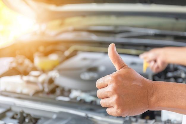 Homem técnico desistindo polegar depois de verificar o nível de óleo do motor
